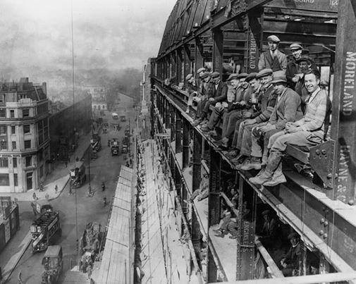 Construction workers on lunch break on the edges of the building they're working on, London, 1929